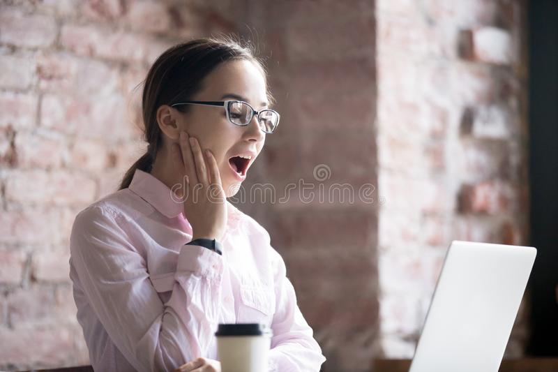Verraste die onderneemster met laptop wegens winst wordt opgewekt stock afbeelding