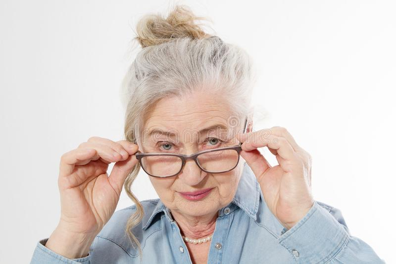 Verraste en schok Hogere vrouw met van het rimpelgezicht en oog zorgglazen die op witte achtergrond worden geïsoleerd Rijpe gezon stock afbeelding