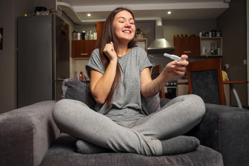 Verraste gelukkige jonge vrouw en zwangerschapstest stock fotografie