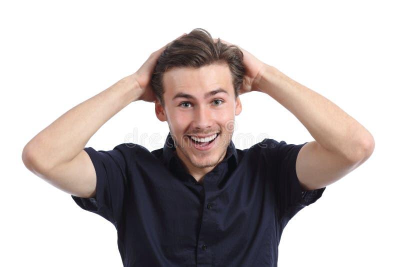 Verraste gelukkige mens die met handen op hoofd glimlachen stock afbeelding