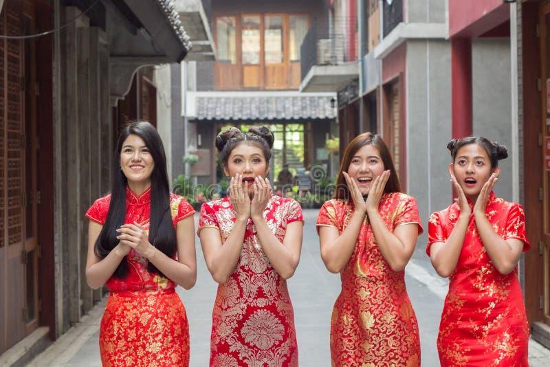 Verraste gelukkige mooie vrouw die omhoog in opwinding, Groep kijken die vrouw cheongsam chainese kleding dragen die iets kijken royalty-vrije stock foto