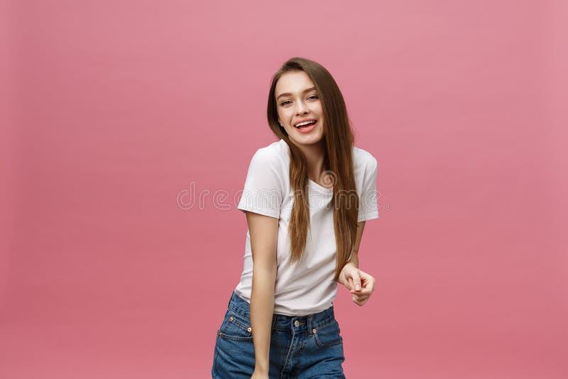 Verraste gelukkige mooie vrouw die in opwinding kijken Isoleer over roze ruimte als achtergrond en exemplaar stock afbeeldingen