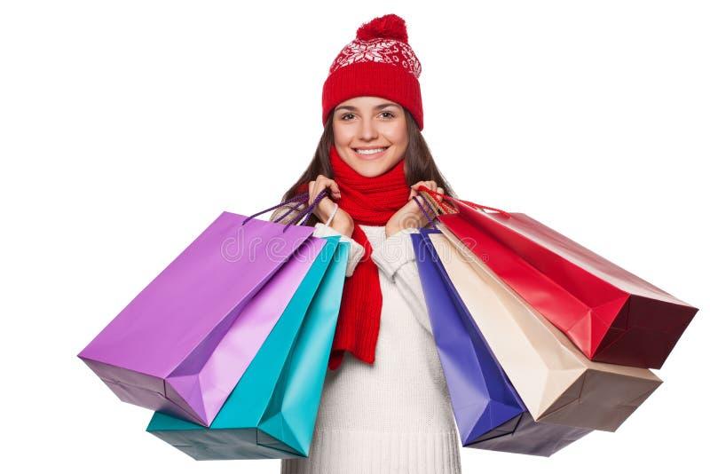 Verraste gelukkige mooie vrouwenholding het winkelen zakken in opwinding Kerstmismeisje op de winterverkoop, op witte achtergrond royalty-vrije stock foto's