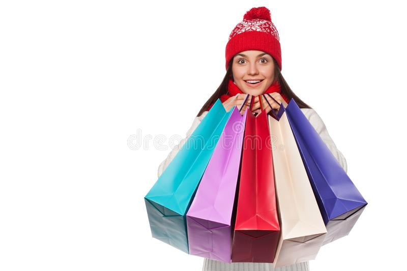 Verraste gelukkige mooie vrouwenholding het winkelen zakken in opwinding Kerstmismeisje op de winterverkoop, op wit wordt geïsole stock foto's