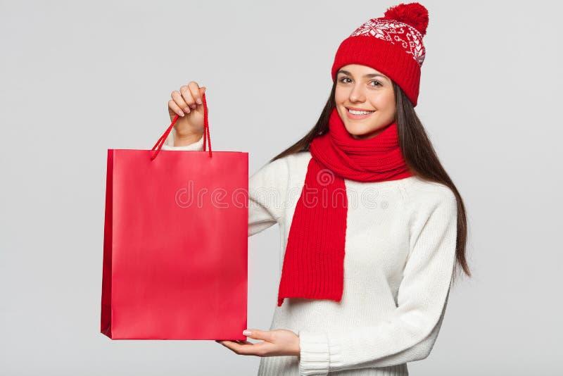 Verraste gelukkige vrouw die rode zak in opwinding, het winkelen houden Kerstmismeisje op de winterverkoop met gift die, op grijs royalty-vrije stock afbeeldingen