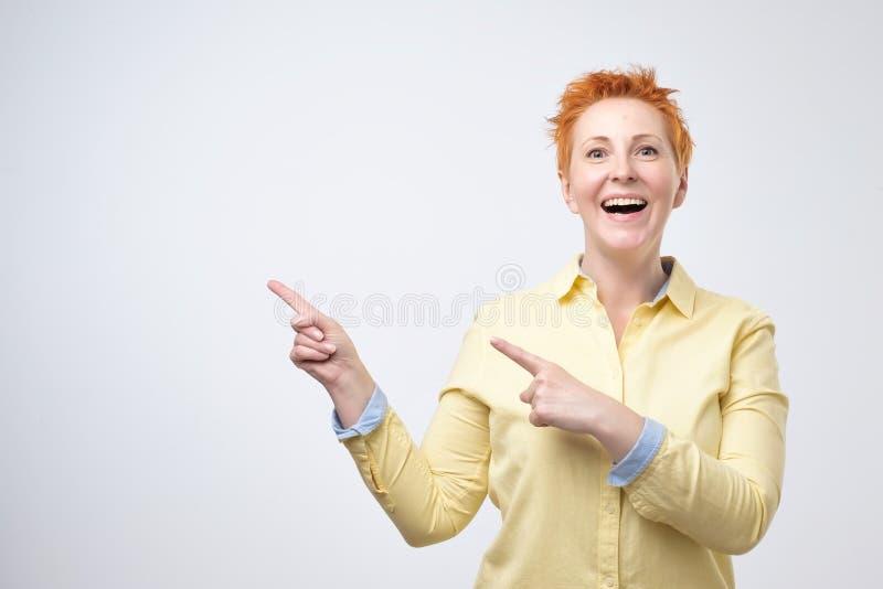Verraste grappige rijpe vrouw in geel overhemd die lege exemplaarruimte met haar vinger grijze achtergrond tonen royalty-vrije stock foto