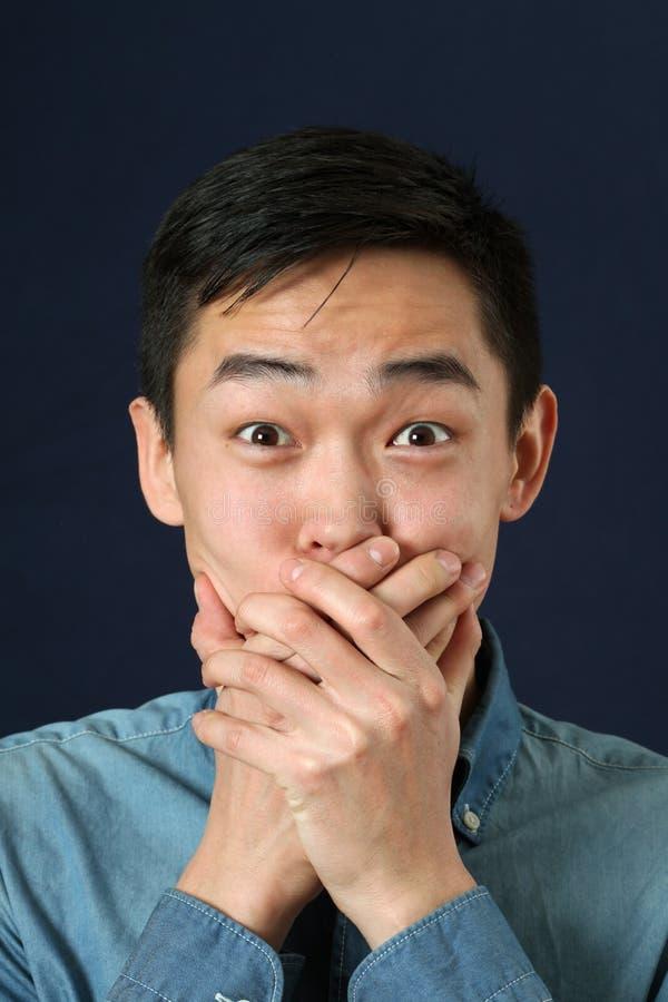 Verraste jonge Aziatische mens die mond behandelen met palmen stock foto's