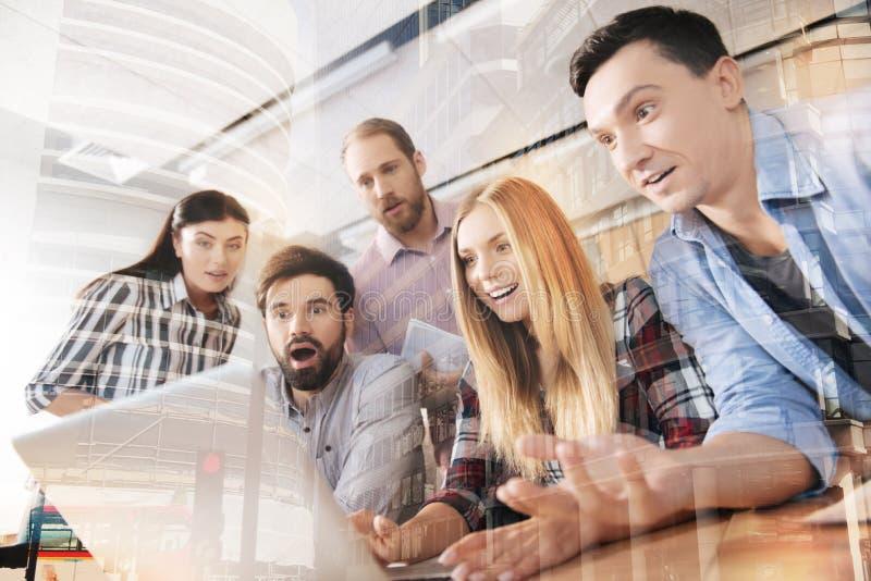 Verraste jonge collega's die laptop in het bureau met behulp van royalty-vrije stock afbeeldingen