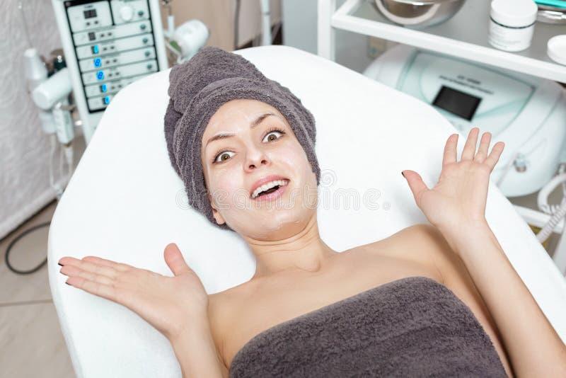 Verraste jonge donkerbruine vrouw die op Kuuroordbehandeling wachten in Kuuroordsalon cosmetology stock afbeelding