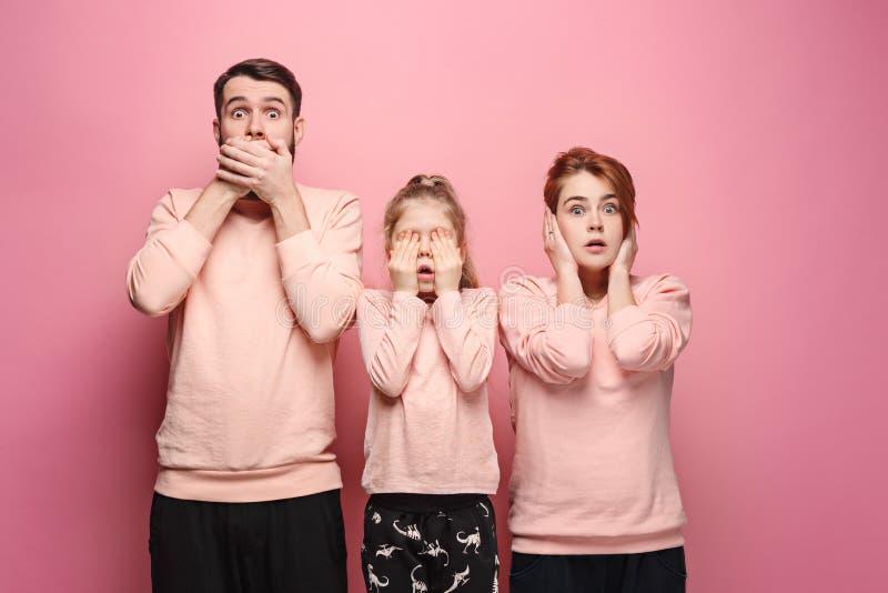 Verraste jonge familie die camera op roze bekijken royalty-vrije stock foto's