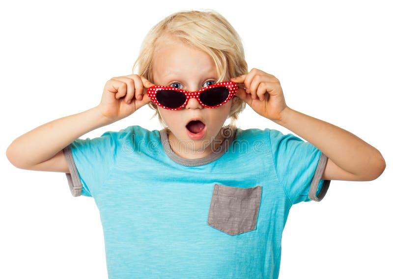 Verraste jonge jongen die zonnebril dragen stock foto