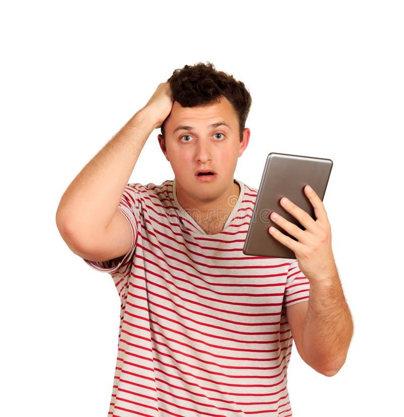 Verraste jonge mens die t-shirt dragen die tabletpc met behulp van emotionele die kerel op witte achtergrond wordt geïsoleerd stock foto