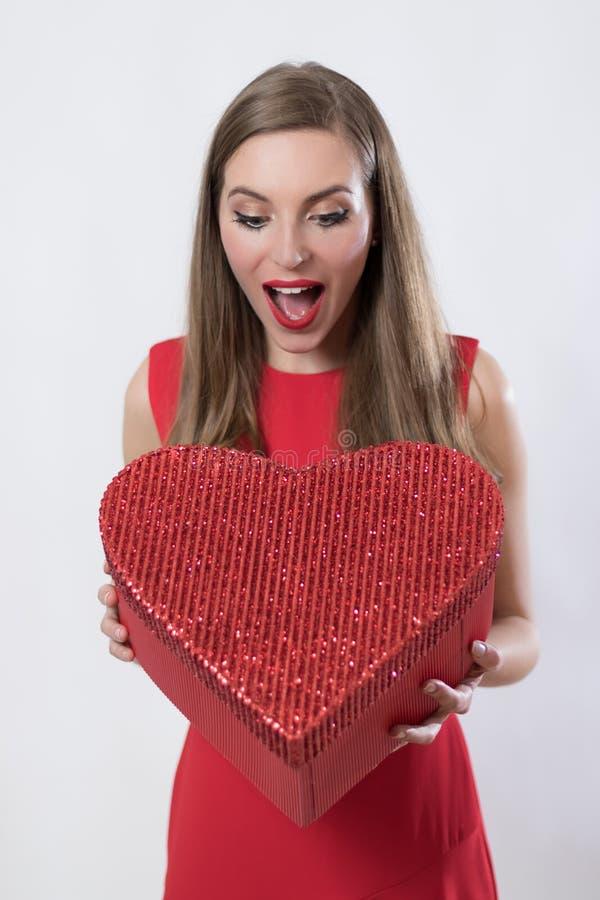 Verraste jonge vrouw die de dag van een grote hart huidige valentijnskaart houden stock foto
