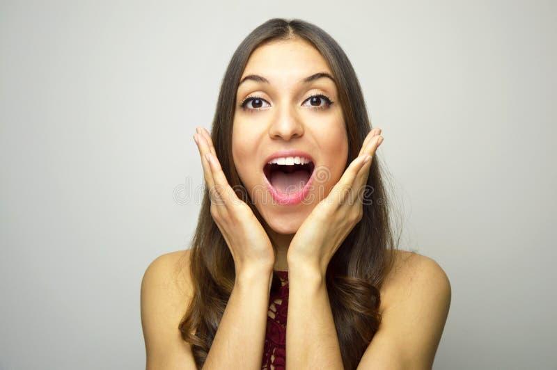 Verraste jonge vrouw die met handen dichtbij open mond camera op grijze achtergrond bekijken royalty-vrije stock foto's