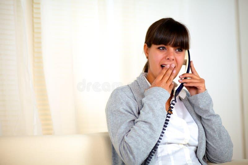 Verraste jonge vrouw die op telefoon converseren royalty-vrije stock fotografie