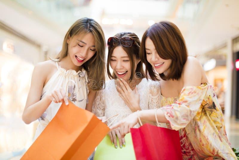 Verraste jonge vrouwen die de shooping zakken kijken stock afbeeldingen