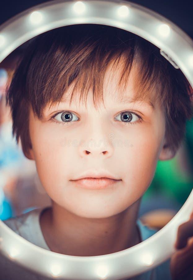 Verraste jongen die de camera door een lichtgevende cirkel als astronaut bekijken royalty-vrije stock foto's