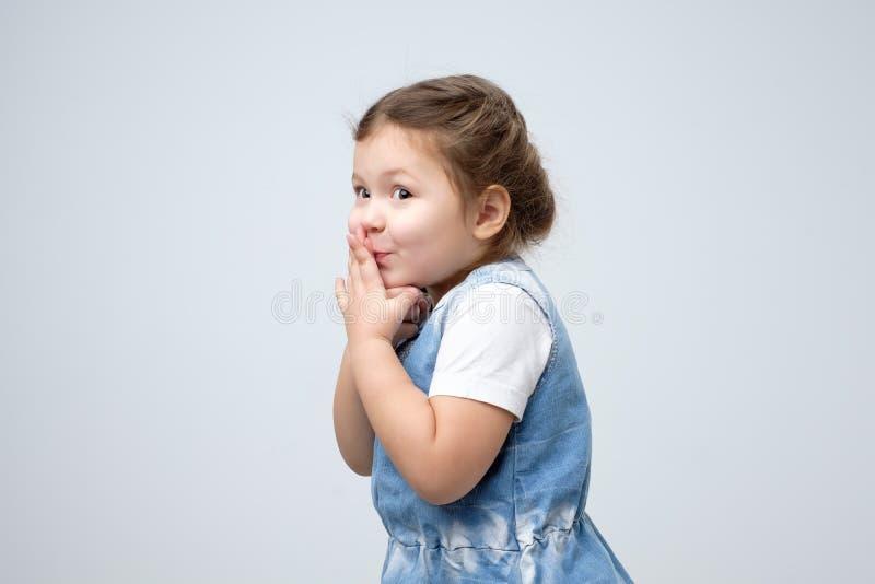 Verraste meisje behandelde mond met haar handen die op gift wachten stock fotografie