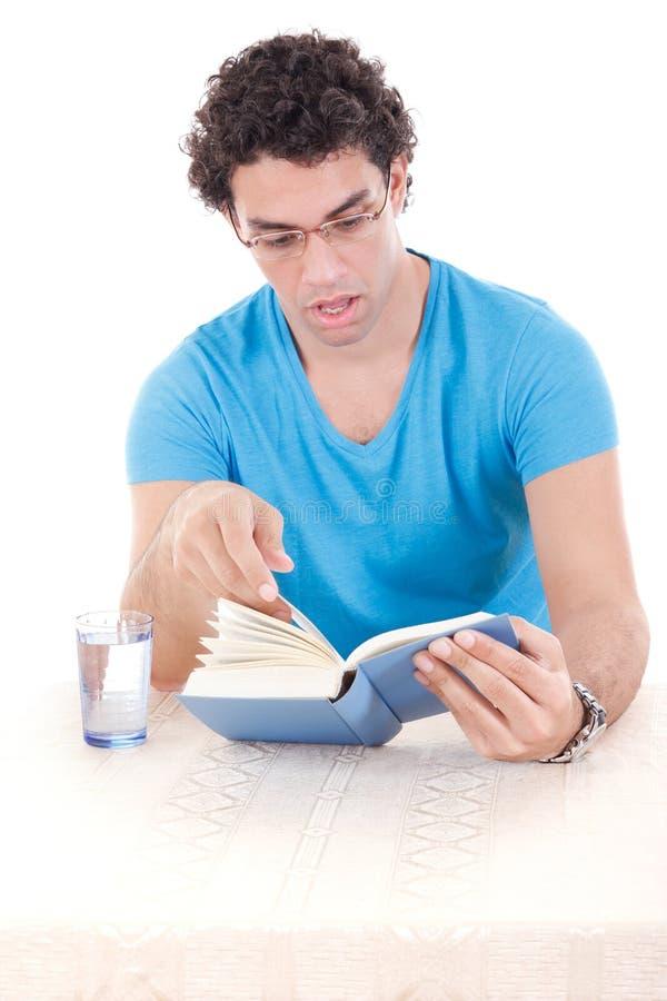 Verraste mens die in blauwe t-shirt met glazen bij lijst zitten en stock fotografie