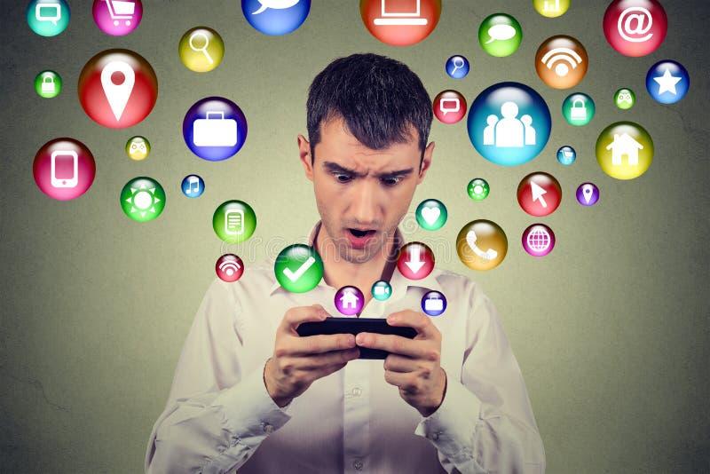Verraste mens die smartphone de sociale media pictogrammen gebruiken die van toepassingssymbolen uit het scherm vliegen stock afbeeldingen