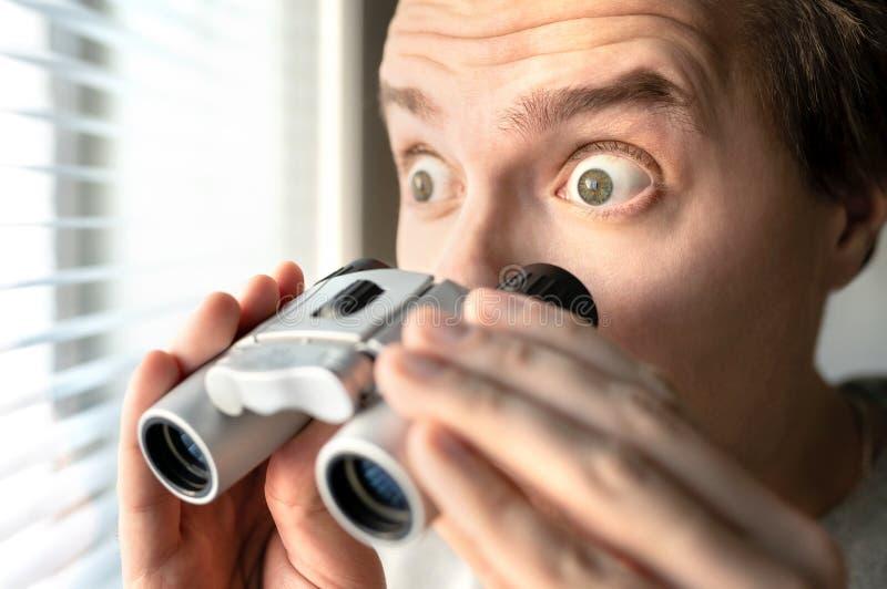 verraste mens met verrekijkers Nieuwsgierige kerel met grote ogen Het bemoeizieke buur besluipen of snooping geheimen, roddel en  stock foto
