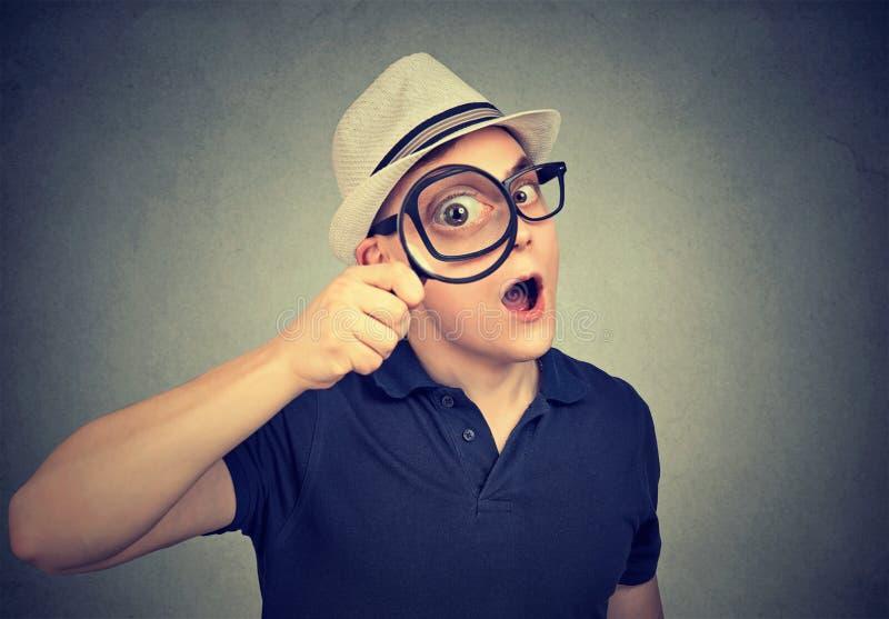 Verraste onderzoeker die door vergrootglas kijken stock fotografie