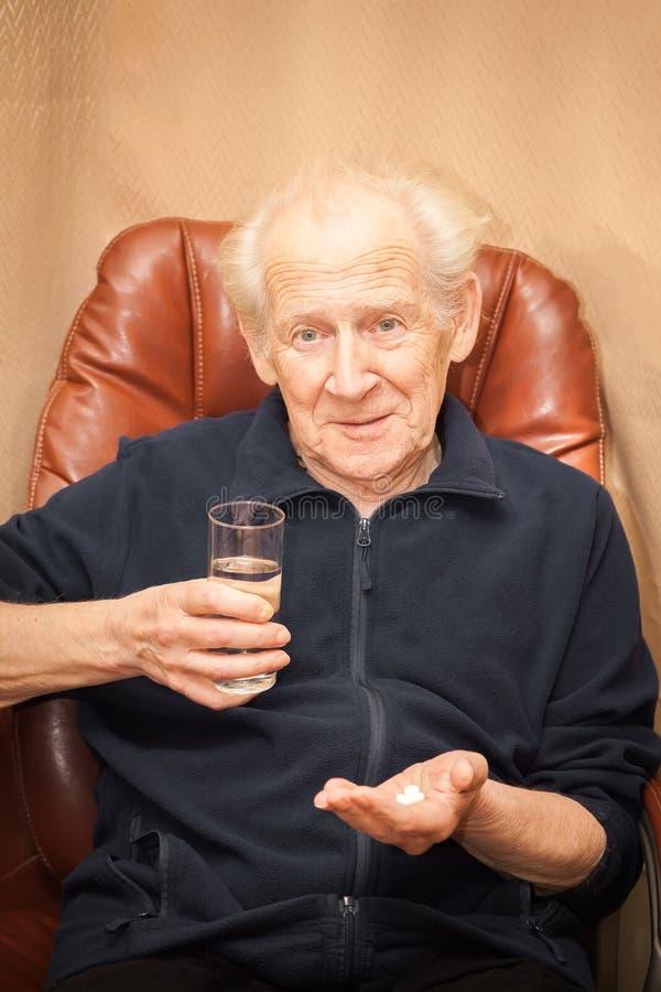 Verraste oude mens met pillen stock afbeelding