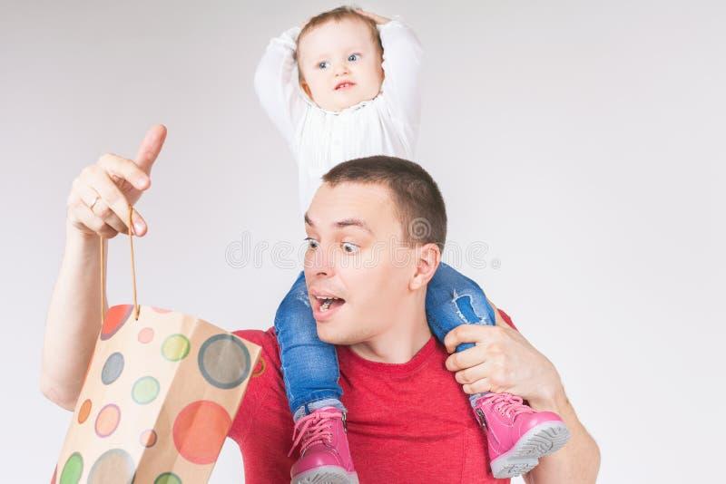 Verraste vader en de grappige zakken van de babyholding met aankopen stock foto