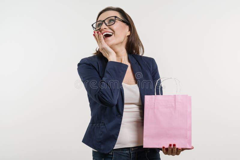 Verraste volwassen vrouw die het winkelen zak, een witte achtergrond kijken royalty-vrije stock fotografie