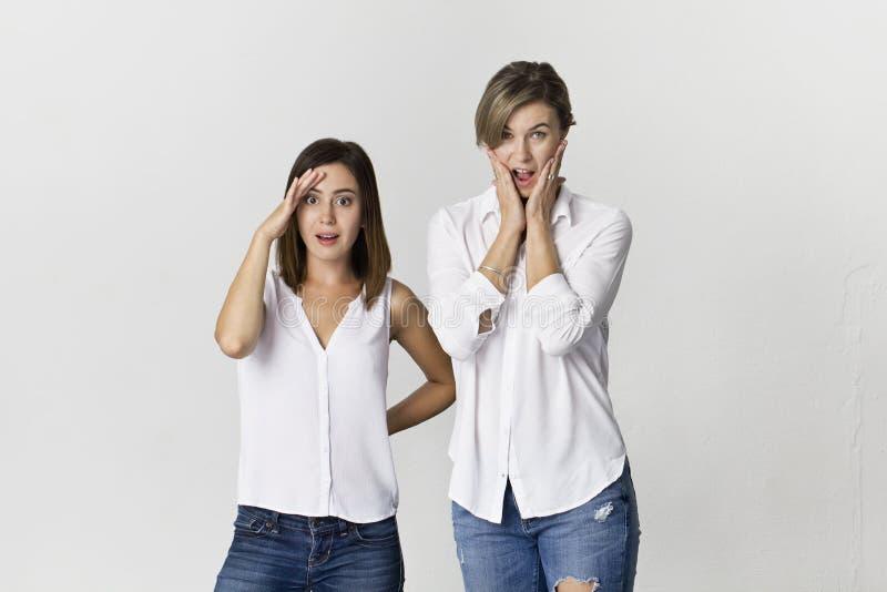 Verraste vrienden die pret hebben bij witte achtergrond Twee meisjes die dragend witte overhemd en jeans bevinden zich royalty-vrije stock afbeelding
