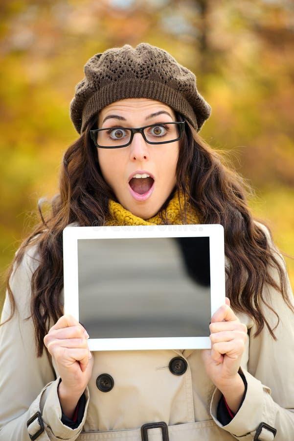Verraste vrouw die het digitale tabletscherm in de herfst tonen stock foto's