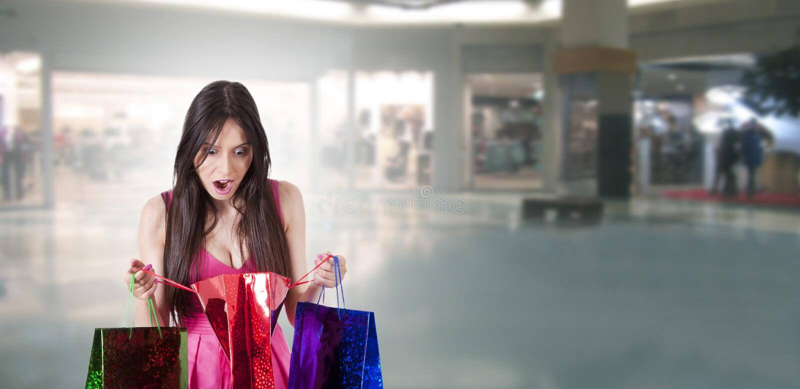 Verraste vrouw die het winkelen bekijkt stock afbeelding