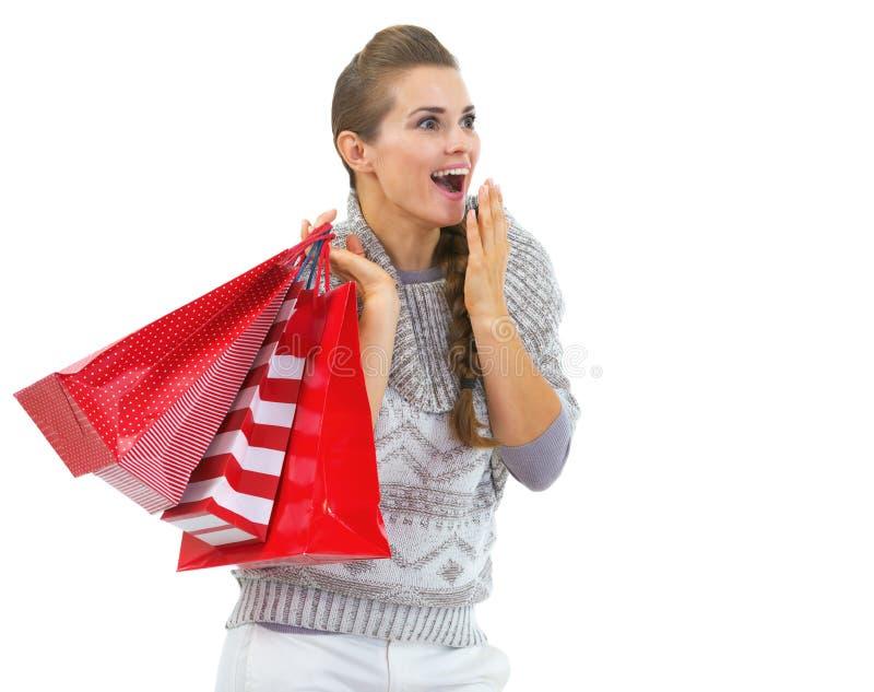 Verraste vrouw die in sweater met het winkelen zakken op exemplaarruimte kijken royalty-vrije stock afbeelding