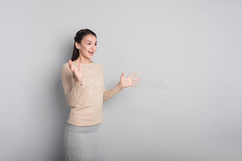 Verraste vrouw die zich op grijze achtergrond bevinden stock afbeeldingen