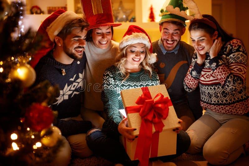 Verraste vrouw en vrienden met Kerstmisgift in het openen van doos stock fotografie