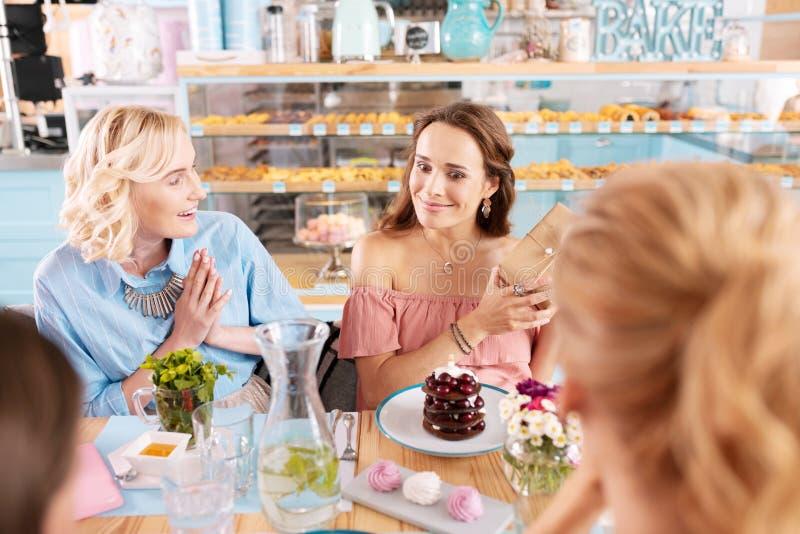 Verraste vrouw gevoel opgewekte het besteden verjaardag met haar vrienden stock afbeelding
