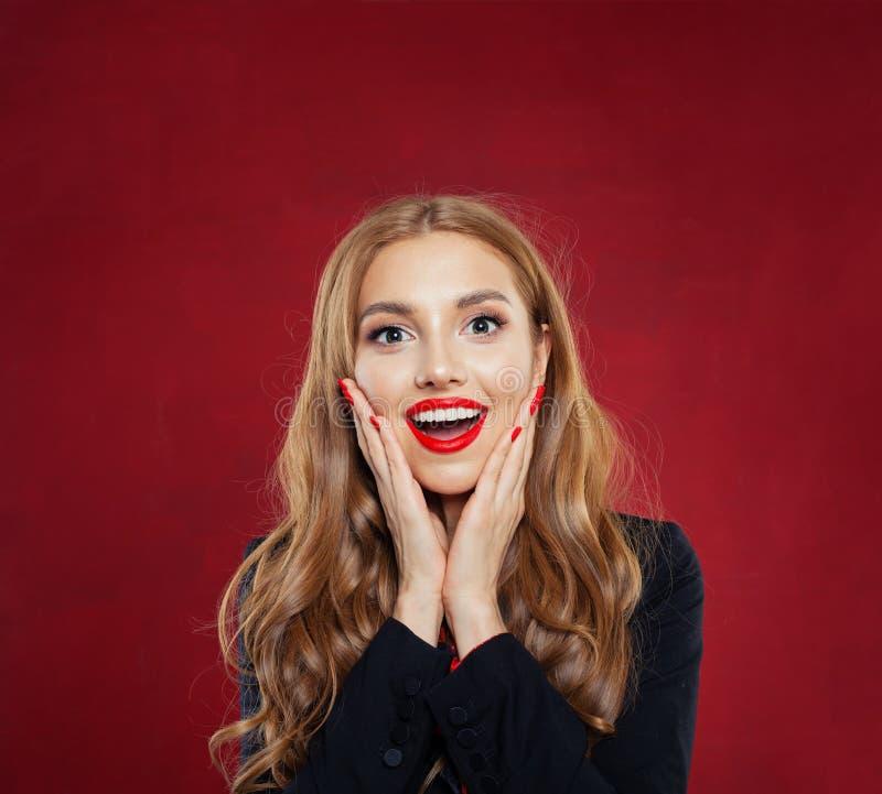 Verraste vrouw met geopende mond op rode achtergrond Gelukkig meisje dat pret heeft Positieve emoties stock foto