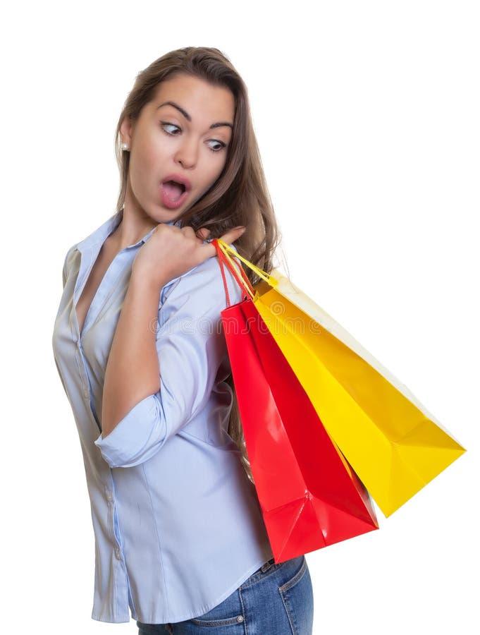 Verraste vrouw met lange donkere haar en het winkelen zakken royalty-vrije stock fotografie