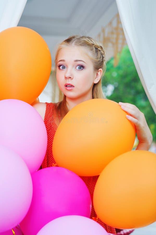 Verraste vrouw met met kleurrijke ballons stock afbeeldingen