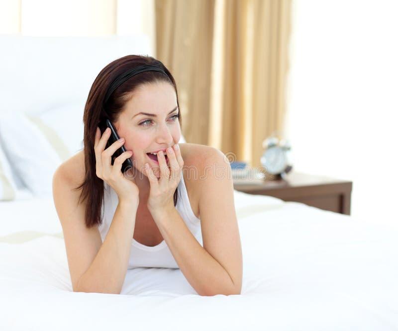 Verraste vrouw op telefoon die op haar bed ligt royalty-vrije stock afbeeldingen