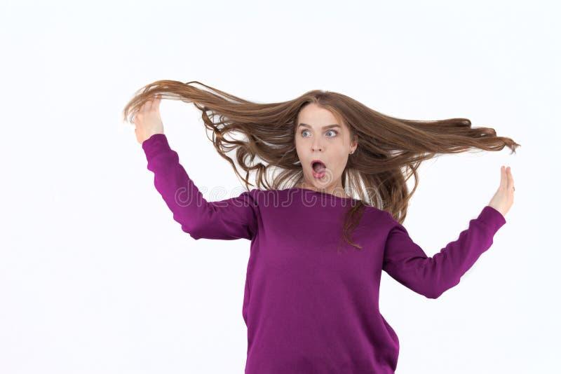 Verraste vrouw, vrouw in schok, verrassing en vliegend haar Blazend haar Het mooie jonge meisje stellen in studio, emoties stock fotografie