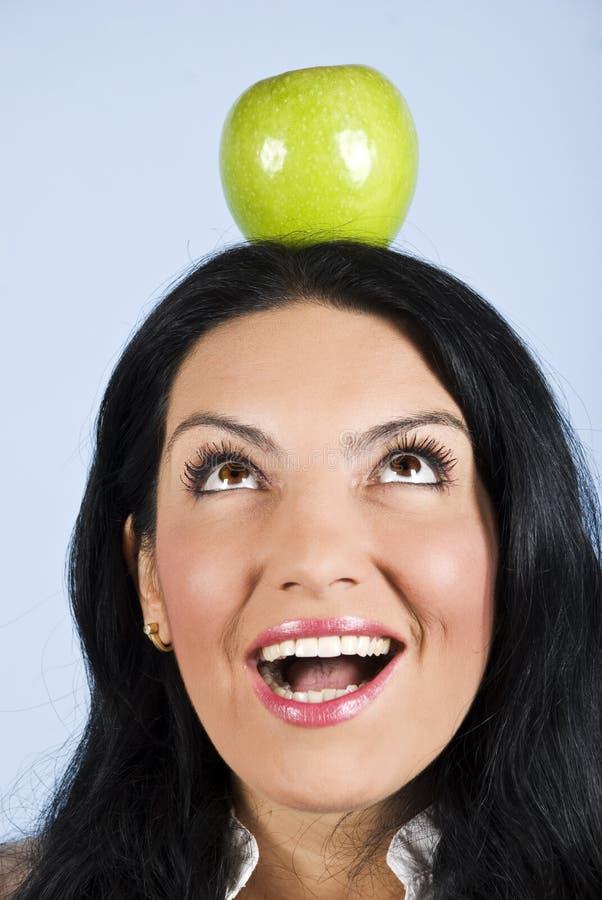 Verraste vrouwengreep een appel op hoofd stock afbeeldingen