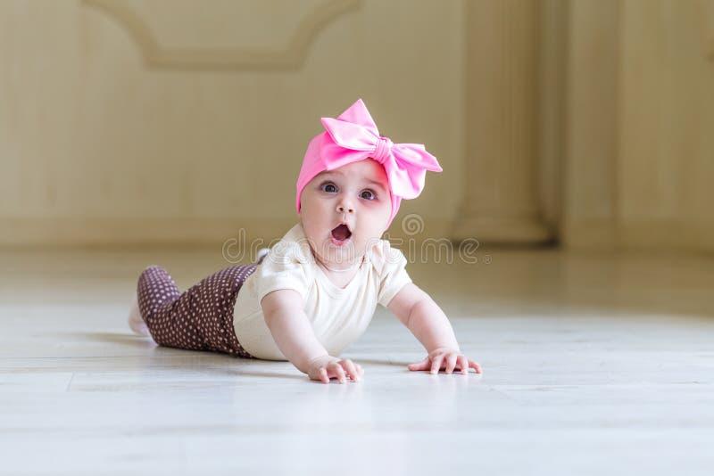 Verraste Weinig Baby op de Vloer in Huis of studiobinnenland Leuke mooie 6 maanden meisjes met een heldere roze boog op a stock foto's