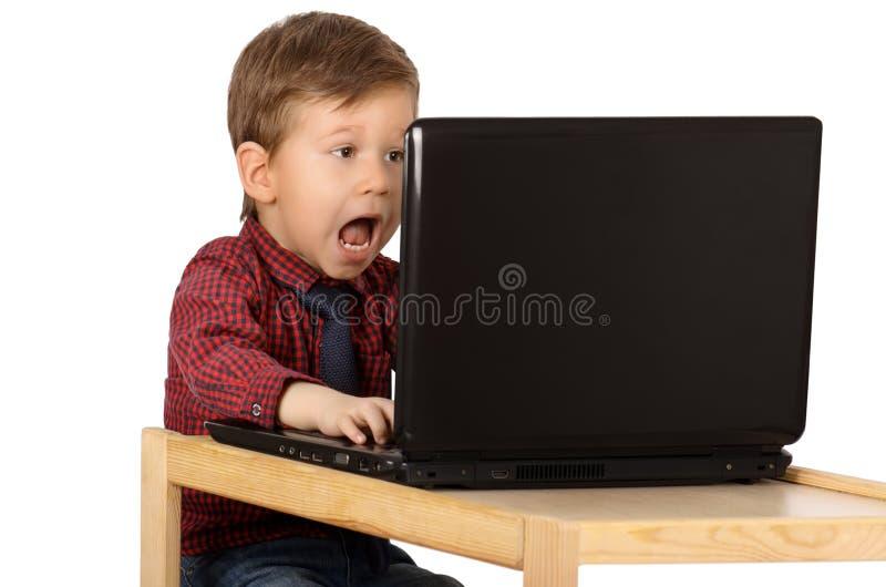 Verraste weinig jongen die aan een laptop computer werken royalty-vrije stock afbeelding