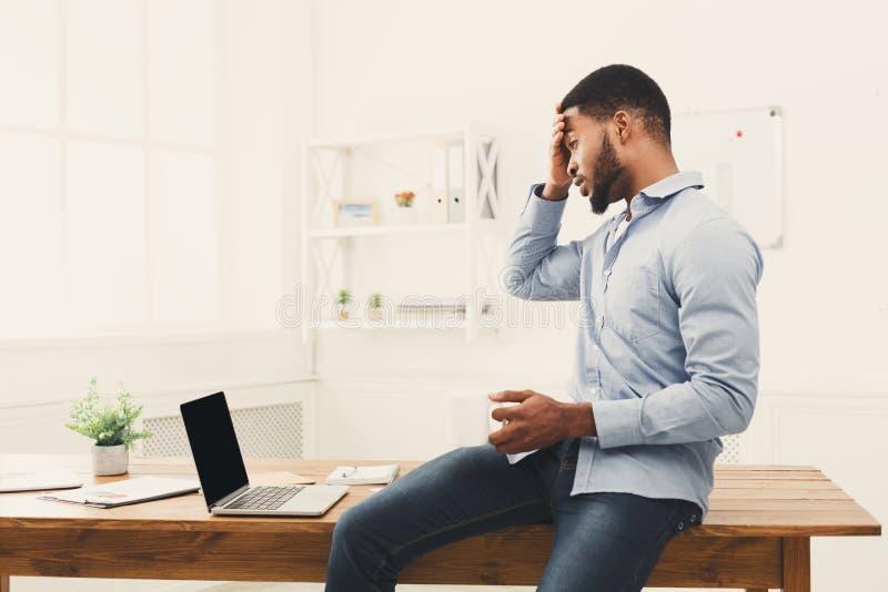 Verraste zwarte zakenman die laptop bekijken stock foto's