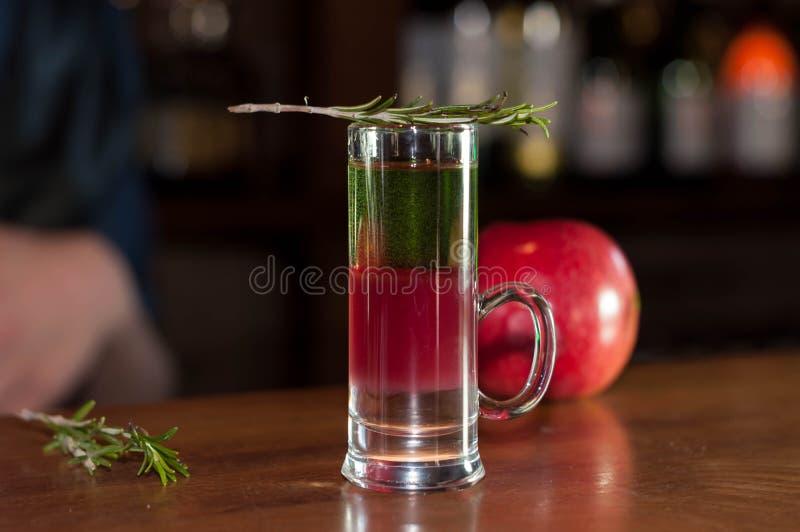Verre à liqueur avec la boisson multicolore d'alcool et romarin sur la pomme rouge proche photographie stock libre de droits