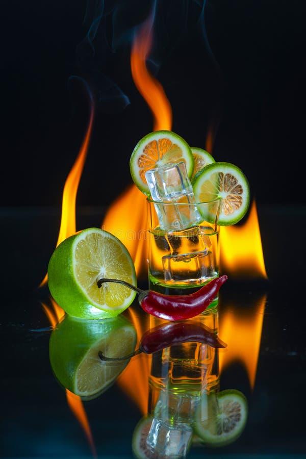 Verre à liqueur vert plein de la glace avec quelques tranches de chaux, moitié de chaux images stock