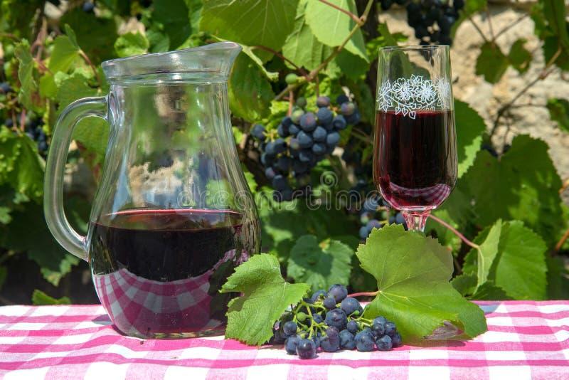 Verre à vin avec la pleine carafe sur une table, image libre de droits