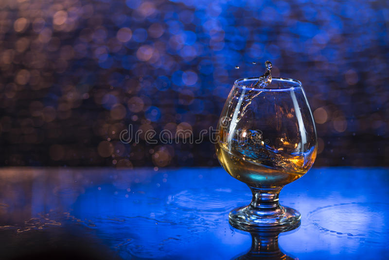 Verre à vin de cognac et d'éclaboussure sur un fond bleu de bokeh photo libre de droits
