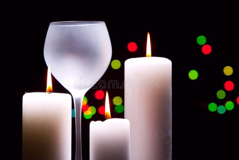 Verre à vin grand et trois bougies photographie stock